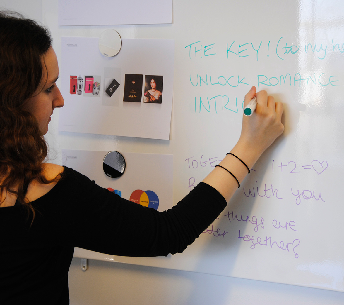 Designer at White Bear Studio writes on white board ideas for startup business, My Date Night
